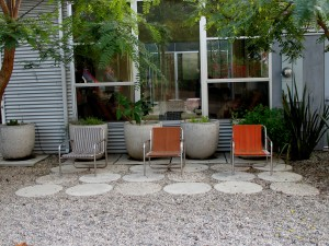 outside of the kitchen, the potted herb garden peaks from behind some handy seating